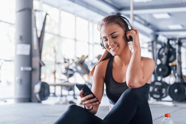 Jong meisje in sportieve kleding en koptelefoon zittend in de sportschool overdag.