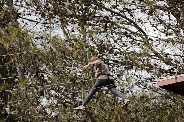 Jong meisje in sportkleding springen van boom naar boom luifel faciliteit bos op de achtergrond