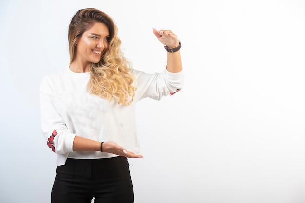 Jong meisje in sportoutfits toont de maatregel