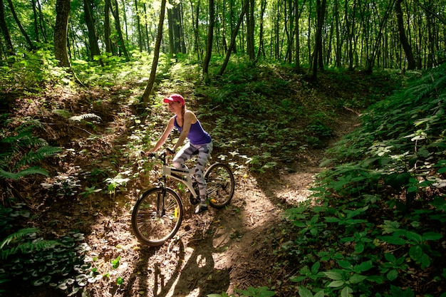 Jong meisje in sportslijtage met fiets het berijden in bos in de zomer