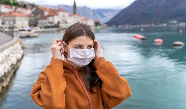 Jong meisje in stadsstraat die beschermend gezichtsmasker draagt