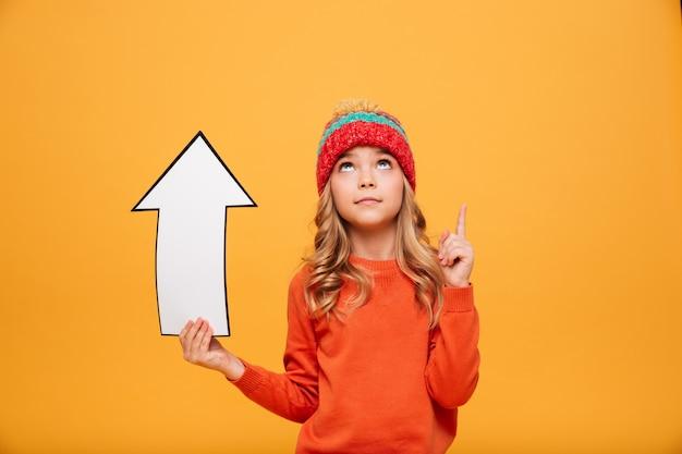 Jong meisje in sweater en hoedenholdingsdocument pijl terwijl het richten en het kijken omhoog over sinaasappel