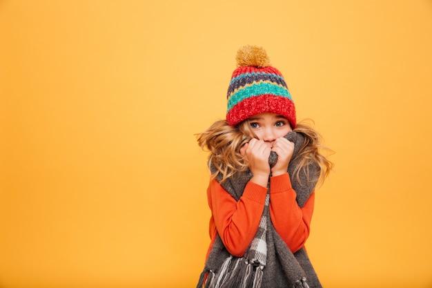 Jong meisje in sweater, sjaal en hoed die koude hebben terwijl het bekijken de camera over sinaasappel