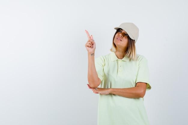 Jong meisje in t-shirt en pet verhogen wijsvinger in eureka gebaar en op zoek verstandig, vooraanzicht.