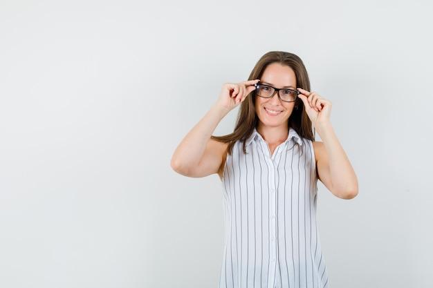 Jong meisje in t-shirt haar bril aan te raken en op zoek vrolijk, vooraanzicht.