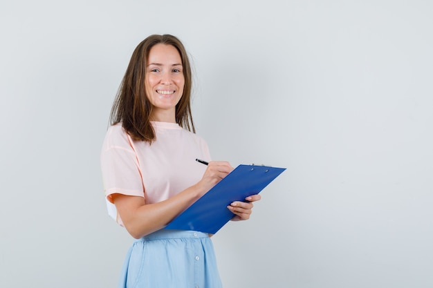 Jong meisje in t-shirt, rok die aantekeningen maakt op klembord en er vrolijk uitziet, vooraanzicht.
