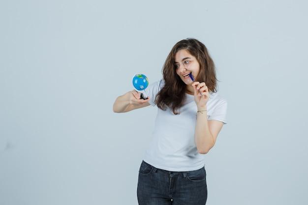 Jong meisje in t-shirt, spijkerbroek die de pen op de mond houdt terwijl ze de wereldbol vasthoudt en er gelukkig, vooraanzicht uitziet.