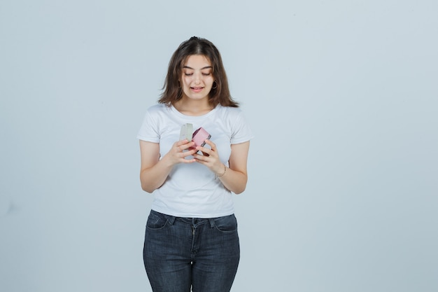 Jong meisje in t-shirt, spijkerbroek geschenkdoos openen terwijl je ernaar kijkt en verbaasd kijkt, vooraanzicht.