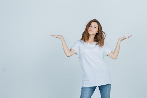 Jong meisje in t-shirt, spijkerbroek schalen gebaar maken en op zoek verleidelijk, vooraanzicht.