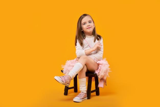 Jong meisje in tule rok en witte pullover zittend op kleine houten kruk