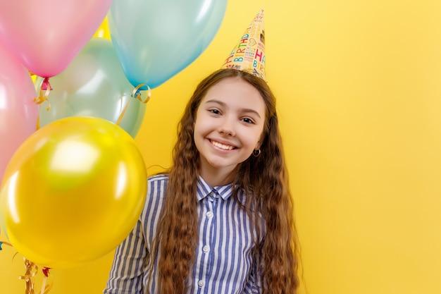 Jong meisje in verjaardagsfeestje met kleurrijke opblaasbare ballons geïsoleerd op een gele muur