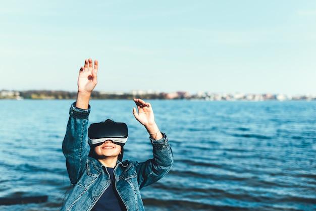 Jong meisje in virtuele werkelijkheidsglazen in het park