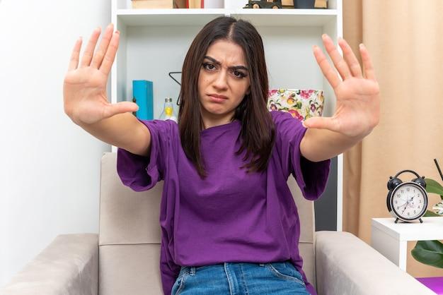 Jong meisje in vrijetijdskleding die met een serieus gezicht kijkt en een stopgebaar maakt met handen zittend op een stoel in een lichte woonkamer