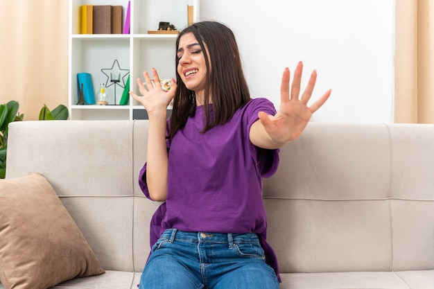Jong meisje in vrijetijdskleding kijkt geïrriteerd en maakt verdedigingsgebaar met handen zittend op een bank in lichte woonkamer
