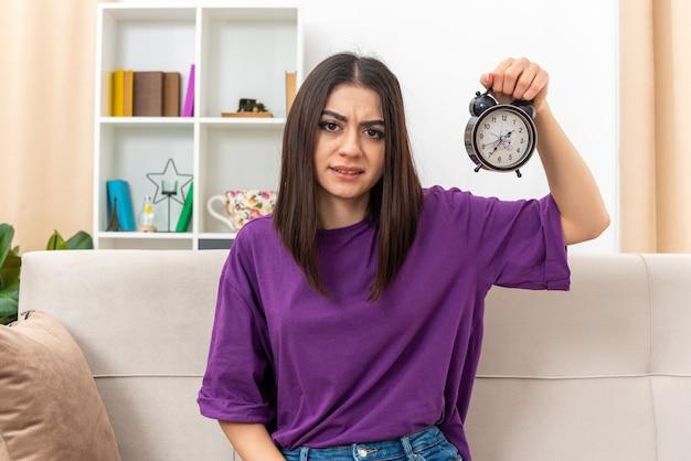 Jong meisje in vrijetijdskleding met een wekker die er verward en ontevreden uitziet terwijl ze op een bank in een lichte woonkamer zit