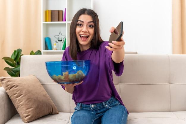 Jong meisje in vrijetijdskleding met kom chips met smartphone die er gelukkig en vrolijk uitziet, breed glimlachend zittend op een bank in lichte woonkamer living
