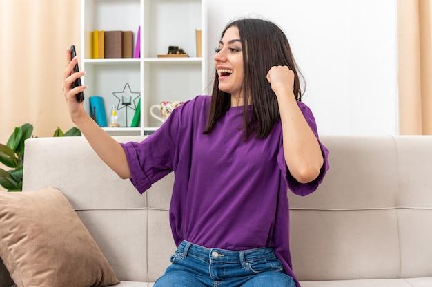 Jong meisje in vrijetijdskleding met smartphone balde vuist blij en opgewonden zittend op een bank in lichte woonkamer