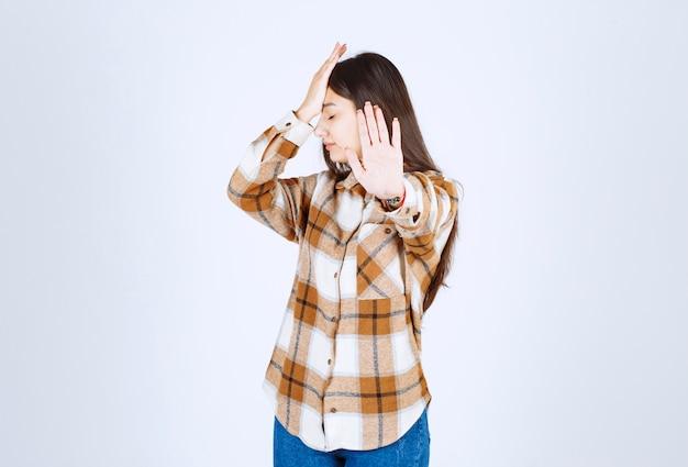 Jong meisje in vrijetijdskleding permanent en stopbord geven op witte muur.