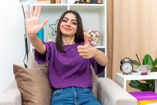 Jong meisje in vrijetijdskleding ziet er gelukkig en positief uit met nummer vijf en duimen omhoog zittend op een stoel in lichte woonkamer living