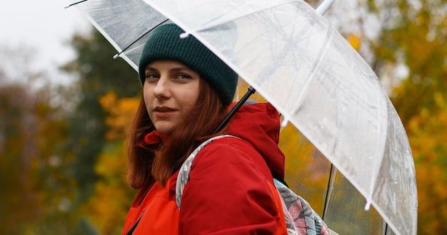 Jong meisje in warme kleren met een transparante paraplu en rugzak op haar rug buiten in de kou