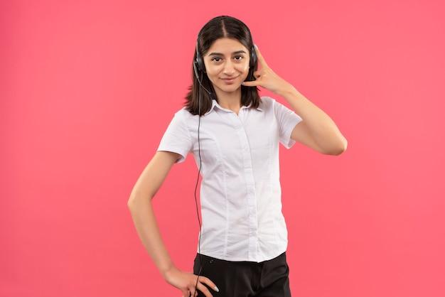 Jong meisje in wit overhemd en koptelefoon, kijkend naar de voorkant bel me gebaar glimlachend staande over roze muur