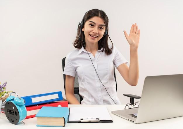 Jong meisje in wit overhemd en koptelefoon, op zoek naar de voorkant met glimlach op gezicht zwaaien met hand zittend aan de tafel met mappen en laptop over witte muur
