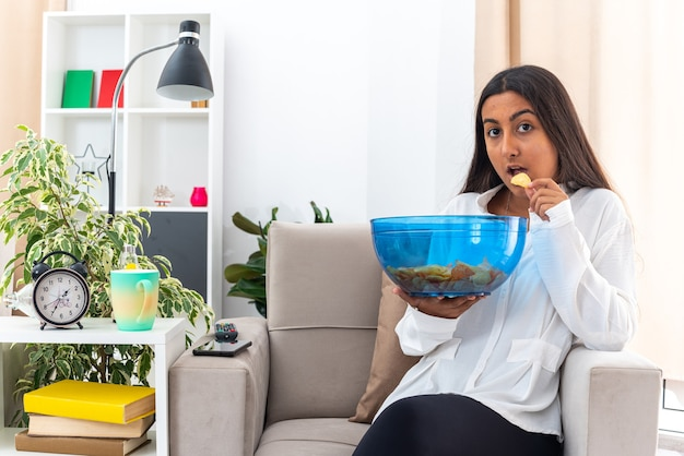 Jong meisje in wit overhemd en zwarte broek met kom chips eten en zittend op de stoel in lichte woonkamer