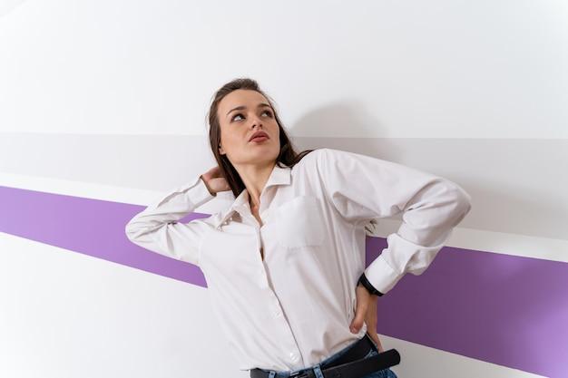 Jong meisje in wit overhemd. vrouw staat in de buurt van witte muur met één hand boven het hoofd. blauwe spijkerbroek, casual stijl.