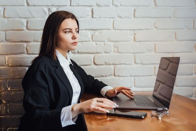 Jong meisje in wit overhemd zittend aan tafel met laptopcomputer en op zoek naar iets. zaken, onderwijs, winkelen en ander concept