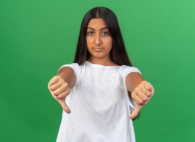 Jong meisje in wit t-shirt camera kijken met een serieus gezicht met duimen naar beneden