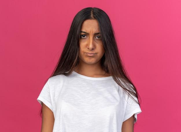 Jong meisje in wit t-shirt camera kijken met ernstig fronsend gezicht staande over roze achtergrond