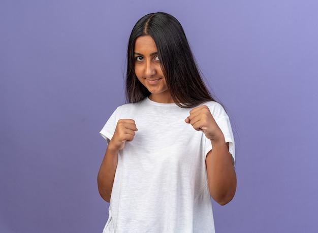 Jong meisje in wit t-shirt camera kijken met gebalde vuisten glimlachend met blij gezicht
