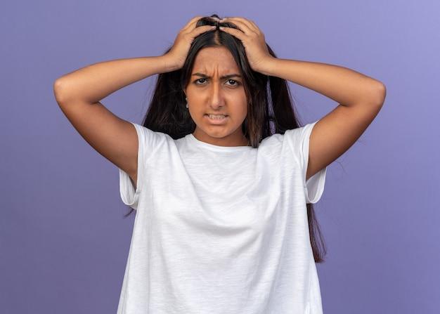 Jong meisje in wit t-shirt dat aan haar haar trekt en naar de camera kijkt met een boos gezicht dat wild over een blauwe achtergrond staat