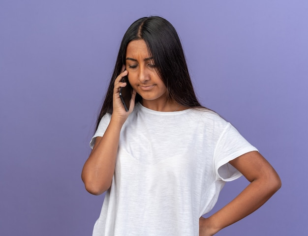 Jong meisje in wit t-shirt dat ontevreden kijkt terwijl ze op een mobiele telefoon praat die over blauw staat