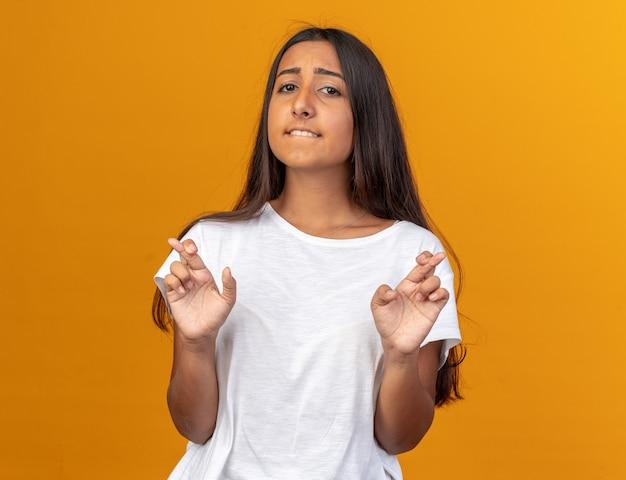 Jong meisje in wit t-shirt die wenselijke wens doet die vingers kruist met hoopuitdrukking die over oranje achtergrond staat