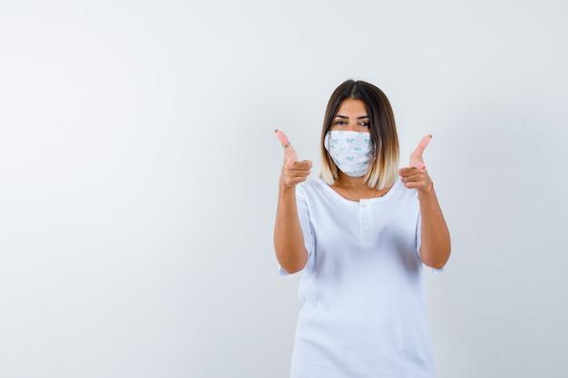 Jong meisje in wit t-shirt en masker dat dubbele duimen toont en vrolijk, vooraanzicht kijkt.