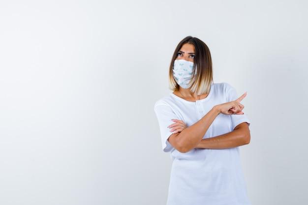 Jong meisje in wit t-shirt en masker dat met wijsvinger naar rechts wijst, hand op arm houdt, omhoog kijkt en peinzend kijkt, vooraanzicht.