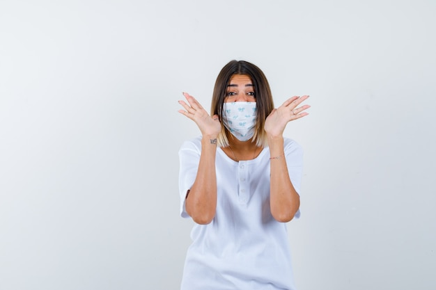 Jong meisje in wit t-shirt en masker hand in hand in de buurt van hoofd en op zoek gelukkig, vooraanzicht.