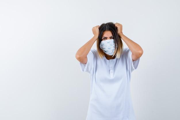 Jong meisje in wit t-shirt en masker hand in hand op het hoofd en op zoek geïrriteerd, vooraanzicht.