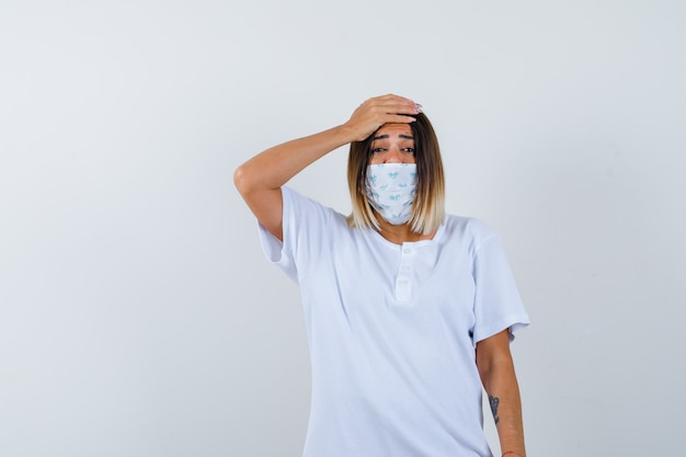 Jong meisje in wit t-shirt en masker hand op het voorhoofd zetten en bezorgd, vooraanzicht kijken.
