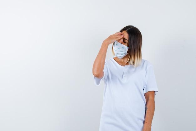 Jong meisje in wit t-shirt en masker hand op voorhoofd zetten en op zoek gekwelde, vooraanzicht.