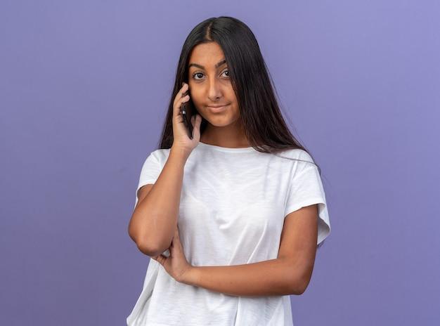 Jong meisje in wit t-shirt glimlachend vriendelijk kijkend naar de camera terwijl ze op een mobiele telefoon praat die over een blauwe achtergrond staat