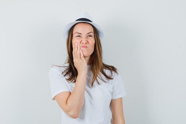 Jong meisje in wit t-shirt, hoed die aan kiespijn lijdt en ongemakkelijk, vooraanzicht kijkt.