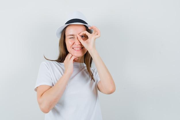 Jong meisje in wit t-shirt, hoed doet ok teken op oog en kijkt vrolijk, vooraanzicht.