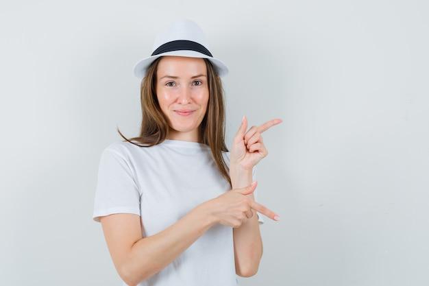 Jong meisje in wit t-shirt, hoed wijzende vingers op en neer en kijkend vrolijk, vooraanzicht.