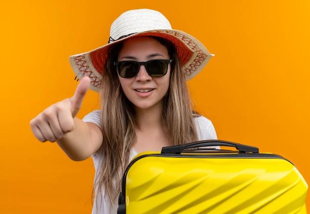 Jong meisje in wit t-shirt in zomer hoed bedrijf reiskoffer glimlachend duimen opdagen