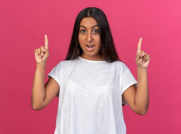 Jong meisje in wit t-shirt kijkend naar camera blij en opgewonden met wijsvingers met een nieuw idee over roze achtergrond
