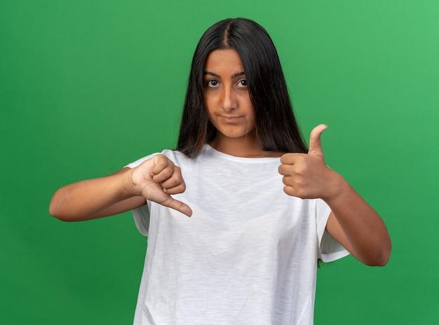 Jong meisje in wit t-shirt kijkend naar camera die ontevreden is met duimen op en neer die over groene achtergrond staat