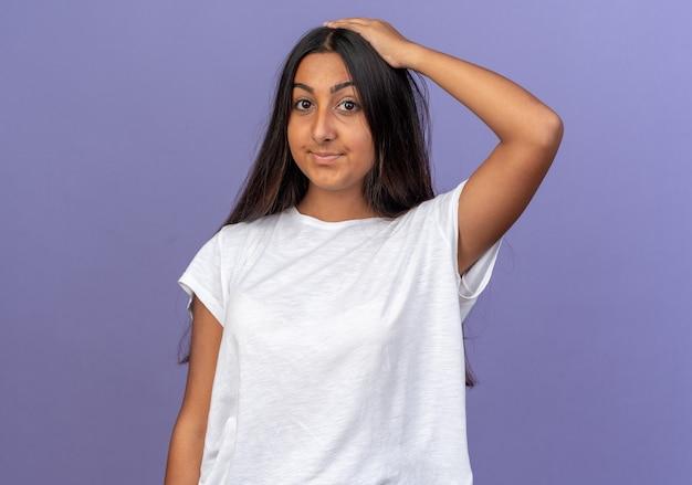 Jong meisje in wit t-shirt kijkend naar camera glimlachend verward met hand op haar hoofd voor vergissing