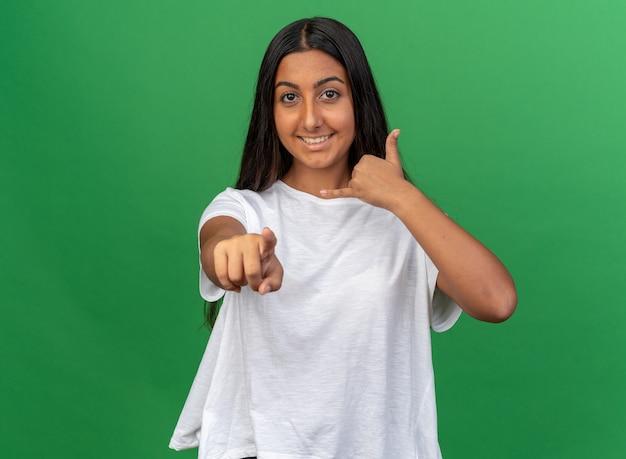 Jong meisje in wit t-shirt kijkend naar camera glimlachend vrolijk tonend bel me gebaar wijzend met wijsvinger naar camera
